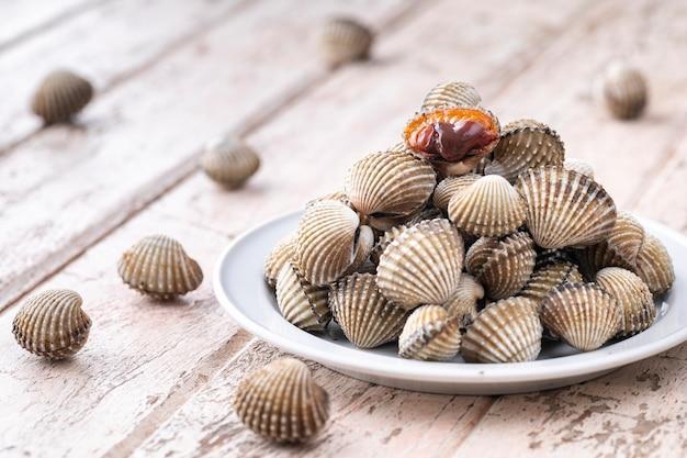 Coques fraîches cuites à la vapeur, coques bouillies dans une assiette en céramique sur fond de texture de bois blanc ancien, menu de recettes de fruits de mer faciles, coque de sang