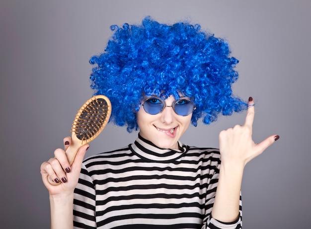 Coquette fille aux cheveux bleus avec un peigne.