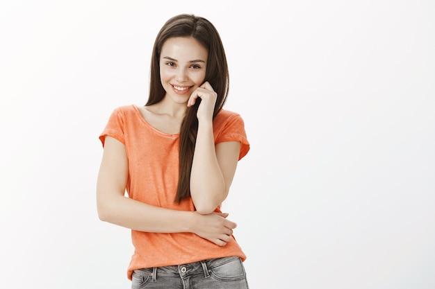 Coquettish et féminine jeune fille souriante et à la séduction