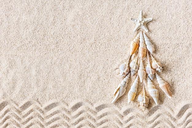Coquillages et arbre de noël étoile de mer sur sable clair