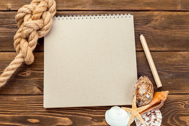 Coquillages et bloc-notes sur une table en bois. vue de dessus avec espace de copie