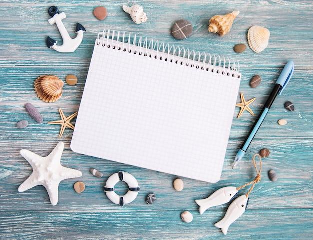 Coquillages et bloc-notes sur une table en bois