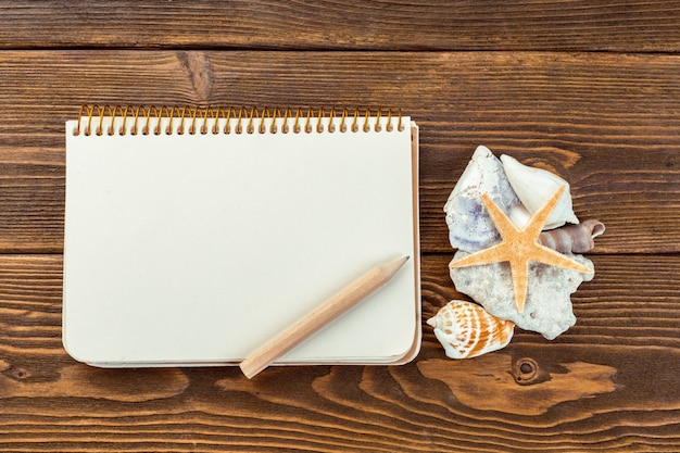 Coquillages et bloc-notes sur une table en bois.