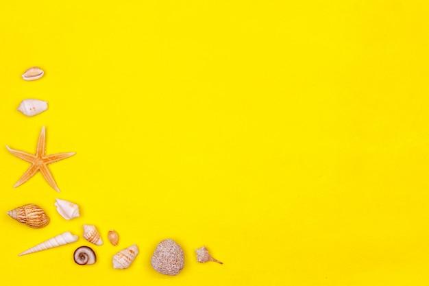 Coquillages, étoiles de mer sur fond jaune. maquette de l'humeur d'été