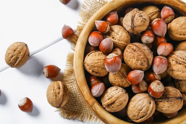 Coquillages et os de noix sur une table en bois blanche.