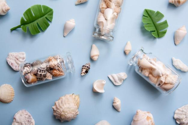 Coquillages plats, mini bouteilles, feuilles tropicales. le concept de la mer, des vacances, des voyages