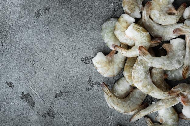 Coquille congelée sur crevettes tigrées ou ensemble de crevettes tigrées asiatiques, sur fond de pierre grise, vue de dessus à plat, avec espace de copie pour le texte