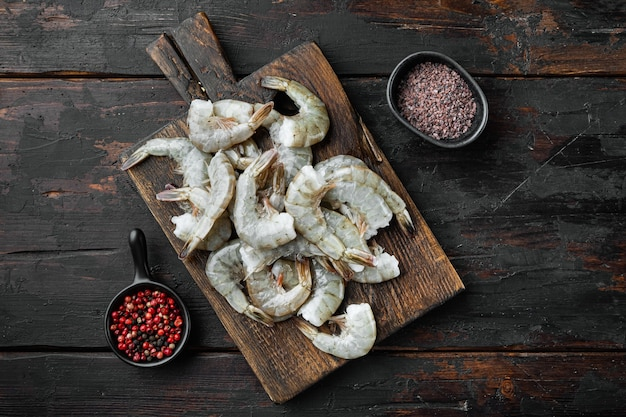 Coquille crue sur l'ensemble de crevettes royales, sur une planche à découper en bois, sur une vieille table en bois foncé, vue de dessus à plat