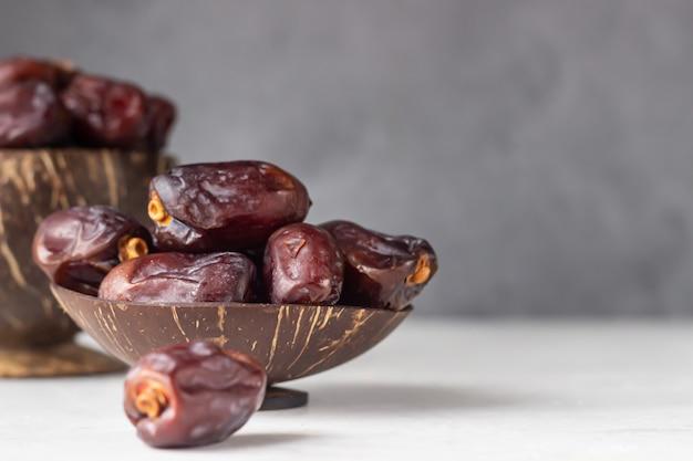 Coquille de noix de coco avec dattes medjool bio sur une surface en béton gris clair
