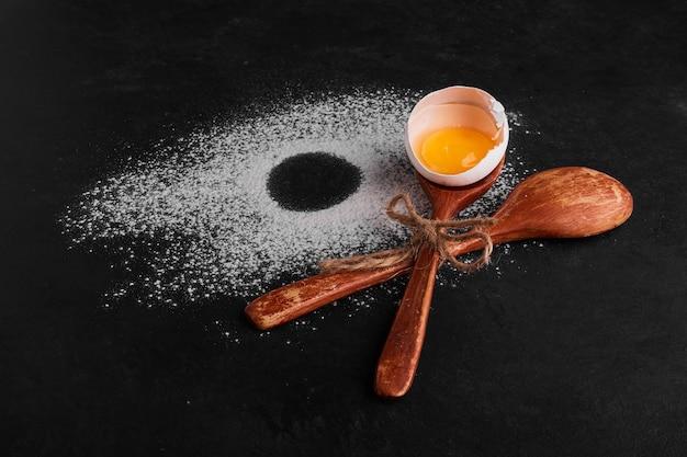 Coquille d'oeuf dans une cuillère en bois sur l'espace de farine.