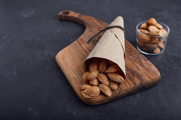Coquilles d'amande dans le papier d'emballage et tasse en verre sur planche de bois sur une surface bleue.