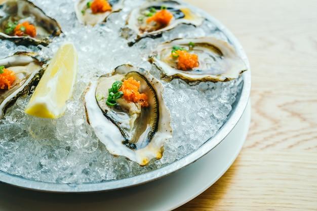 Coquilles d'huîtres crues et fraîches au citron