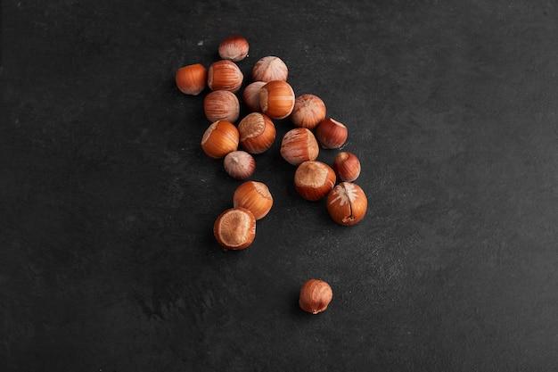 Coquilles de noix sur une surface noire.
