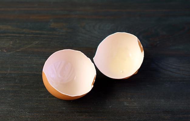 Coquilles d'œufs fêlées isolés sur table en bois noir