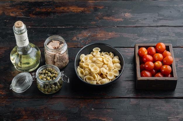 Coquilles de pâtes au thon ingrédients sur table en bois noir