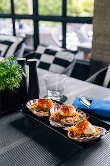 Coquilles saint-jacques grillées et salade de pomelo épicée servies dans une assiette noire.