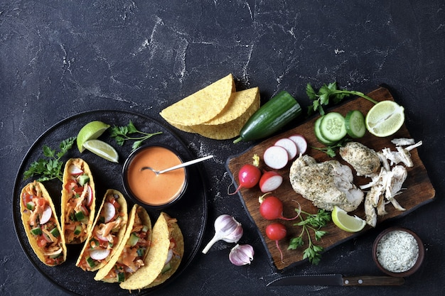 Coquilles de taco de poulet au maïs buffalo chargées de légumes verts frais et de légumes sur une plaque noire avec de la lime et de la sauce buffalo