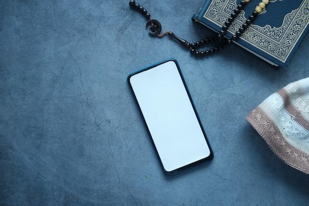 Coran et chapelet de livre saint de téléphone intelligent sur le fond noir