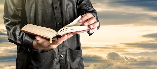Coran dans la main - livre saint des musulmans