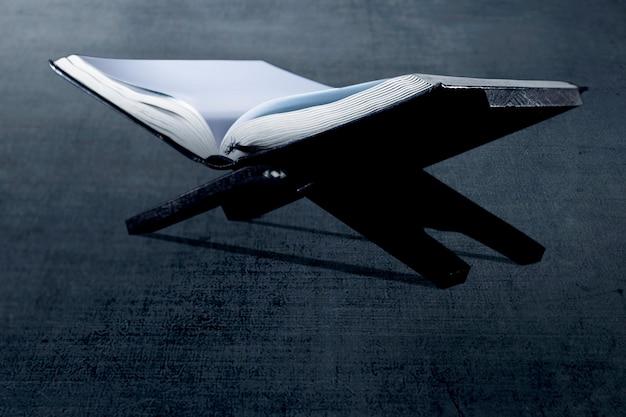 Coran ouvert sur un napperon en bois sur le sol noir