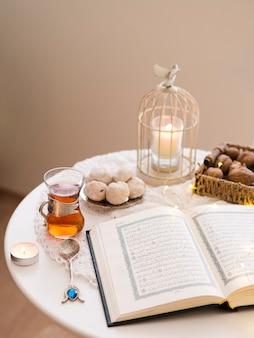 Coran ouvert sur la table entouré de pâtisseries et de thé