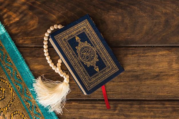 Coran et perles près de tapis