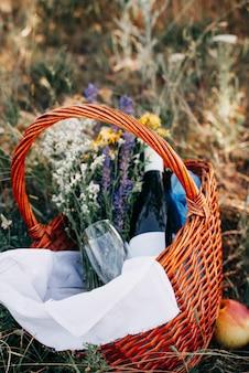 Corbeille de fruits et vin sur un plaid lors d'un pique-nique romantique