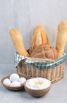 Corbeille à pain, œuf et farine sur une surface en pierre