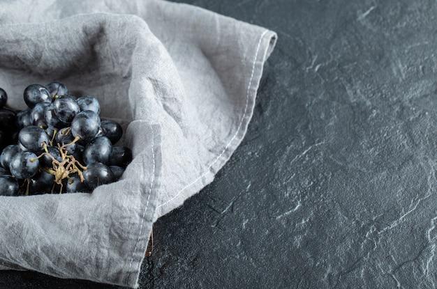 Corbeille de raisins avec nappe grise sur marbre.