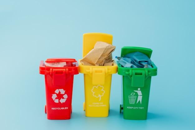 Corbeilles jaunes, vertes et rouges avec symbole de recyclage sur bleu