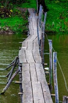 Corde ancienne et endommagée et pont de planches de bois au-dessus de la petite rivière