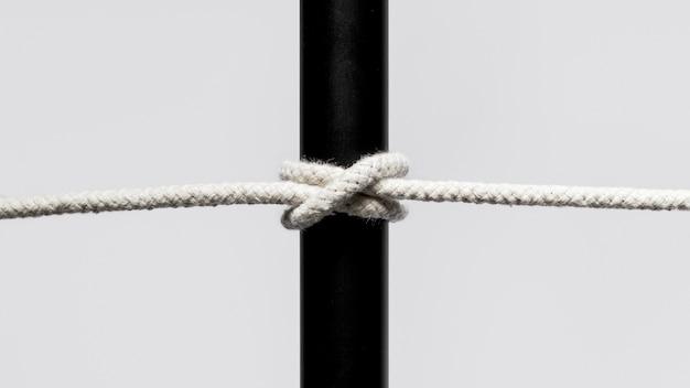 Corde de coton torsadée entourant une barre noire