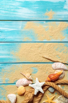 Corde de mer avec de nombreux coquillages sur le sable de la mer sur un fond en bois bleu. vue de dessus