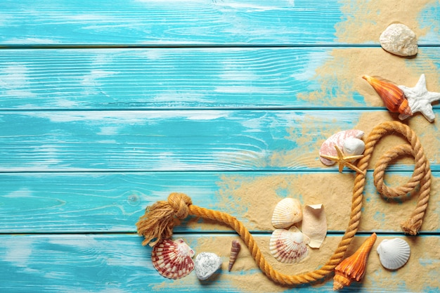 Corde de mer avec de nombreux coquillages sur le sable de la mer sur un fond en bois bleu