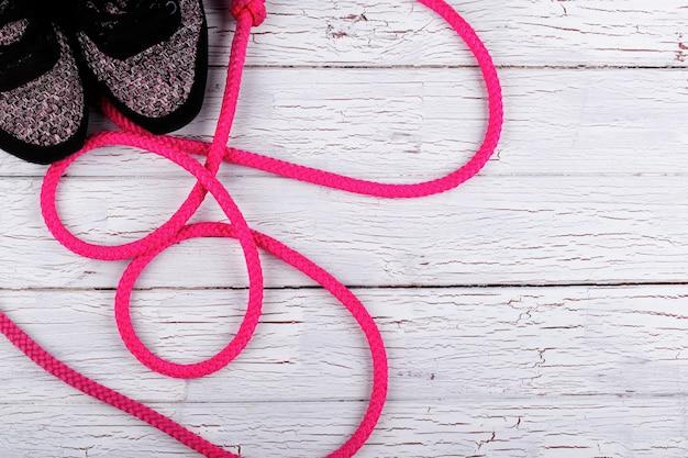 La corde rose passe par des snickers noirs sur le plancher blanc