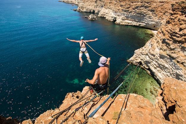 Corde sautant d'une falaise avec une corde dans l'eau. l'océan. mer. montagne.