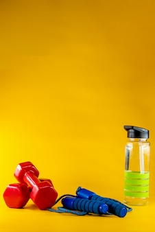 Corde à sauter, haltères et bouteille d'eau