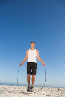 Corde à sauter joyeux homme sportif