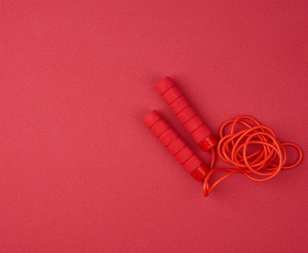 Corde à sauter rouge se trouve sur un tapis de sport rouge en néoprène, close up