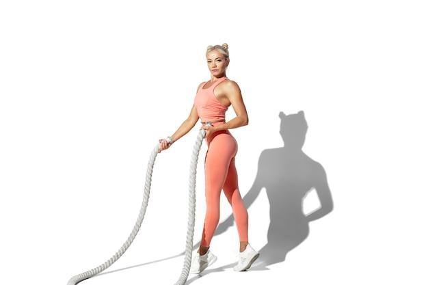 Cordes. belle jeune athlète féminine pratiquant sur le mur blanc du studio
