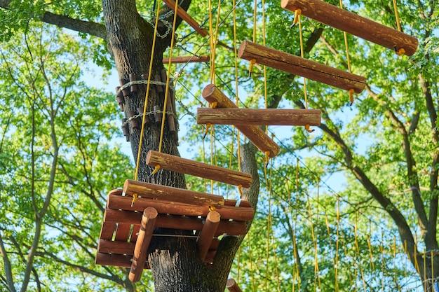 Les cordes hautes font l'expérience du parc d'arbres aventure. parcours sur route de corde dans les arbres