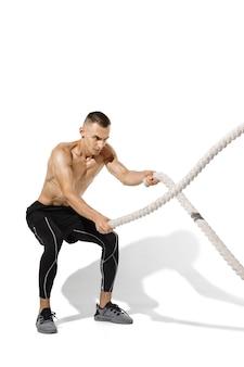 Cordes. jeune athlète masculin élégant pratiquant sur le mur blanc du studio