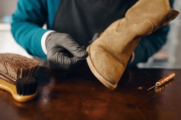 Le cordonnier affûte la semelle de la chaussure, service de réparation de chaussures