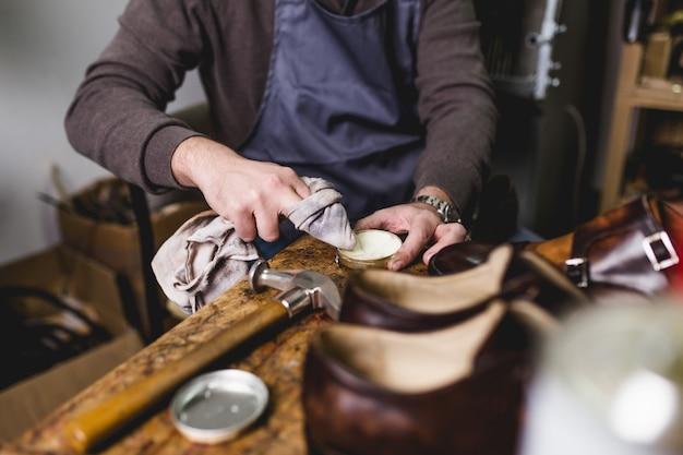 Cordonnier en atelier de polissage de nouvelles belles chaussures en cuir faites à la main.
