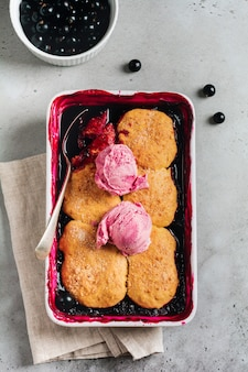 Cordonnier aux framboises et cassis avec glace à la framboise dans un plat allant au four. pâtisseries de tarte aux fruits maison. fond vintage gris. vue de dessus.