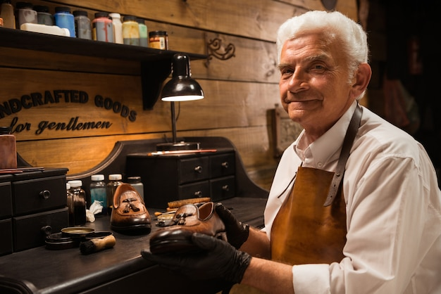 Cordonnier souriant mature en atelier de fabrication de chaussures