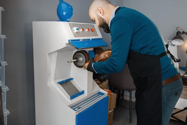 Le cordonnier traite la chaussure sur la machine d'émeri, la réparation de chaussures