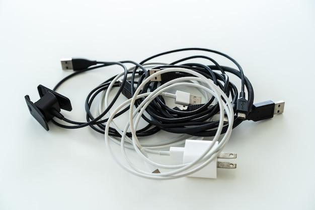 Les cordons d'alimentation usb vintage enroulés sur la table blanche à partir de l'angle supérieur se bouchent. divers câbles universal serial bus ou câble usb et adaptateur de charge usb sur la table.