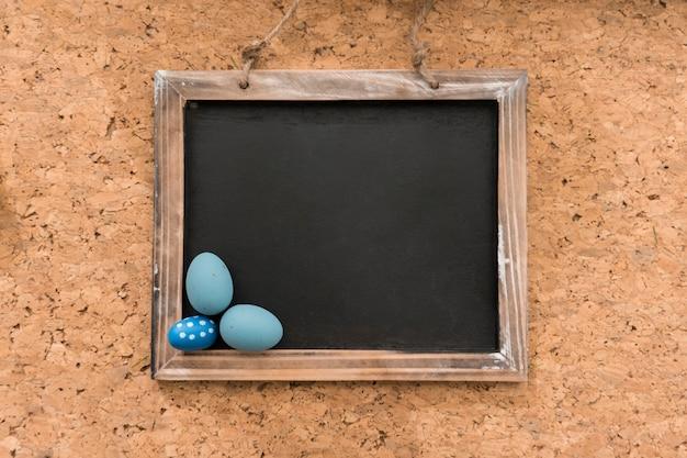 Cork background avec de l'ardoise et des œufs de pâques bleu