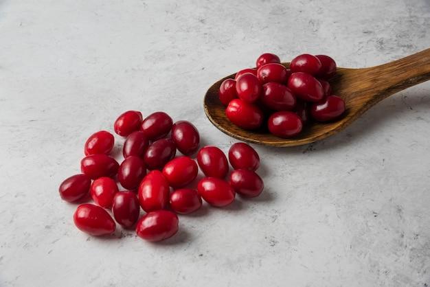 Cornels rouges dans une cuillère en bois.